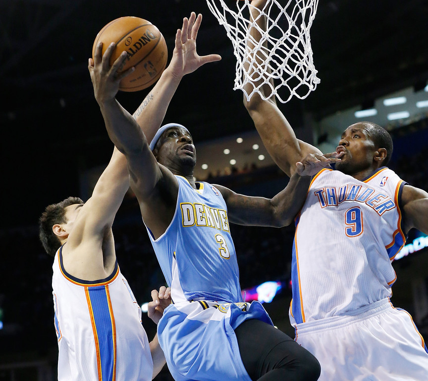 . Denver Nuggets guard Ty Lawson (3) is fouled by Oklahoma City Thunder center Steven Adams as he shoots between Adams and forward Serge Ibaka (9) in the first quarter of an NBA basketball game in Oklahoma City, Monday, Nov. 18, 2013. (AP Photo/Sue Ogrocki)