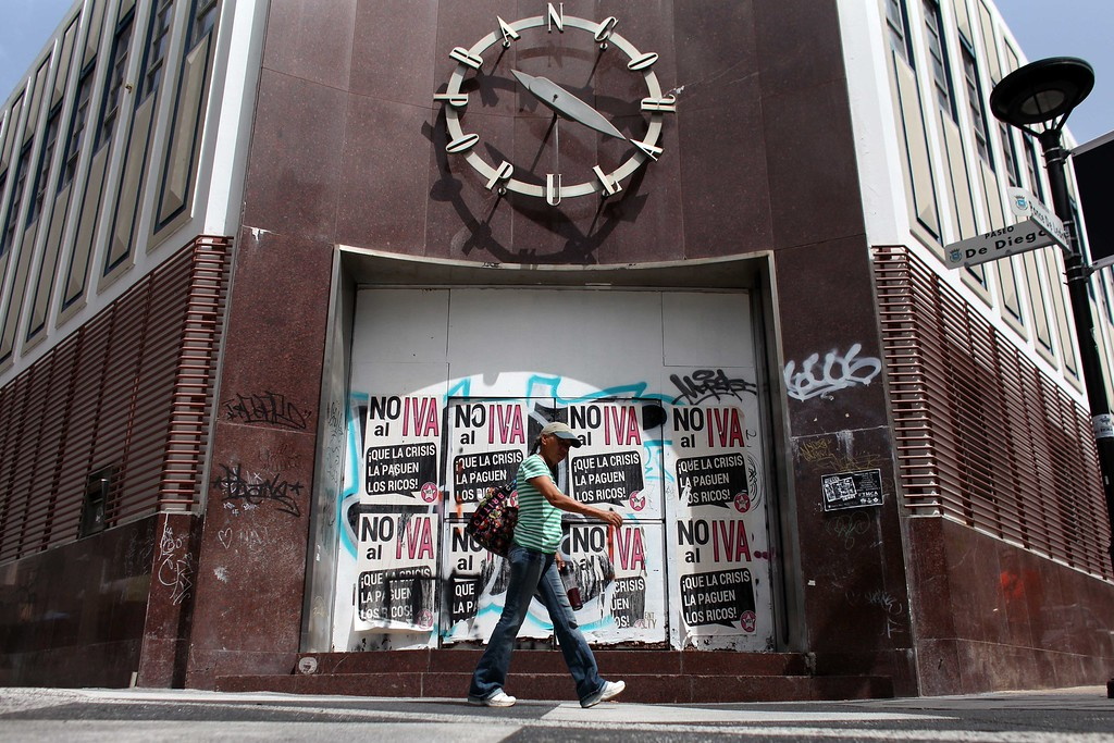 ". A woman walks in front of a closed down bank in the neighborhood of Rio Piedras in San Juan, Puerto Rico, Monday, June 29, 2015. The bills on the closed bank doors read in Spanish ""No to the value added tax. Let the rich pay for the crisis.\"" International economists released a critical report on Puerto Rico\'s economy Monday on the heels of the governor\'s warning that the island can\'t pay its $72 billion public debt. (AP Photo/Ricardo Arduengo)"