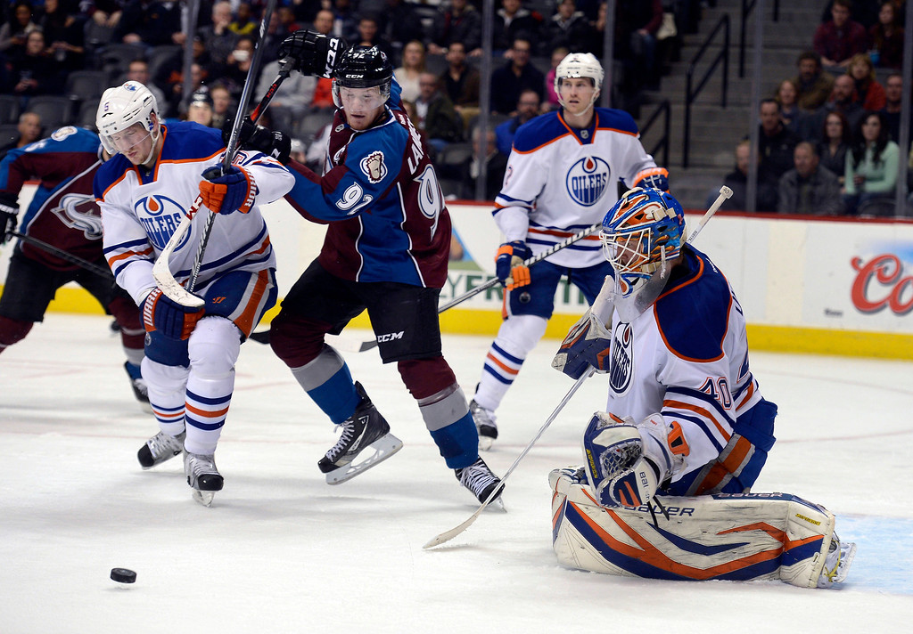. Gabriel Landeskog (92) of the Colorado Avalanche and Ladislav Smid (5) of the Edmonton Oilers battle for the puck after Devan Dubnyk (40) of the Edmonton Oilers made a save during the first period March 12, 2013 at Pepsi Center. (Photo By John Leyba/The Denver Post)