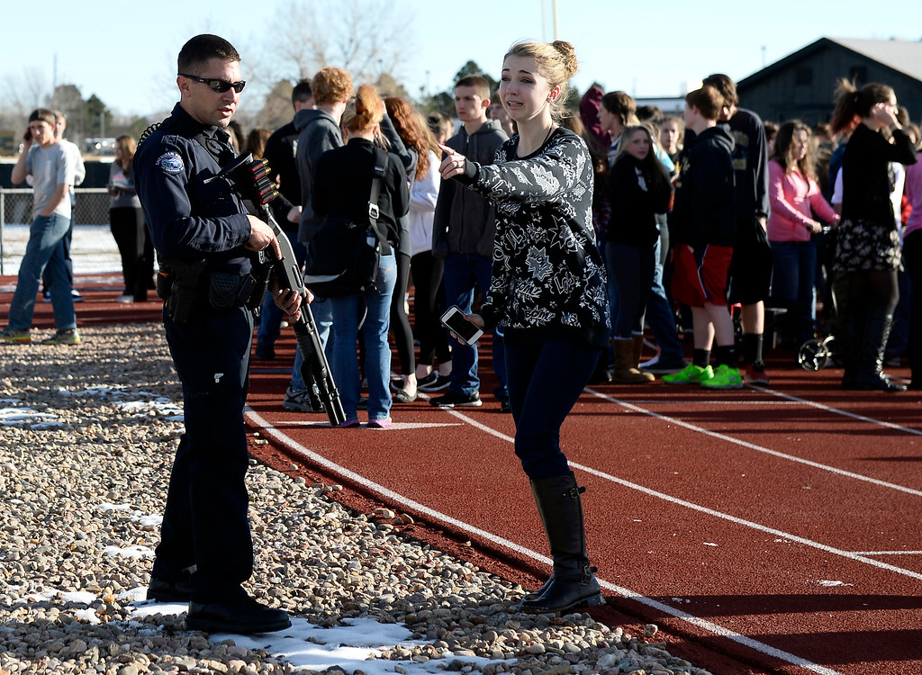 . CENTENNIAL, CO - DECEMBER 13: A student is stopped by an officer from looking for her parents as students stand out side on the football field after a gunman was spotted inside Arapahoe High School December 13, 2013. The gunman was targeting a teacher at the school. The gunman shot two students in the process and then turned the gun on himself. (Photo by John Leyba/The Denver Post)
