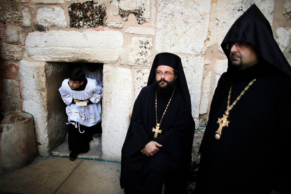 . Orthodox Christian priests (R) wait for the arrival of the Latin Patriarch of Jerusalem Fouad Twal at the entrance of the Church of the Nativity, the site revered as the birthplace of Jesus, in the West Bank city of Bethlehem on December 24, 2012. REUTERS/Ammar Awad