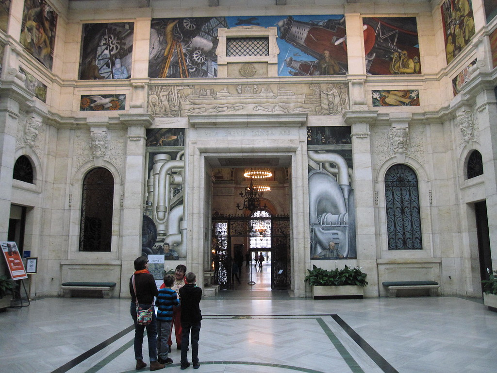 . This Dec. 5, 2014 photo shows visitors near the Detroit Industry Murals at the Detroit Institute of Arts. The murals were done in the 1930s by Diego Rivera as a tribute to Detroit�s manufacturing industry, and  Rivera spent time studying the River Rouge Ford car factory. The museum�s collection was at one point threatened with a sale to help fund Detroit�s pension obligations, but finalization of the city�s bankruptcy last week included a deal that protects the art. (AP Photo/Beth J. Harpaz)