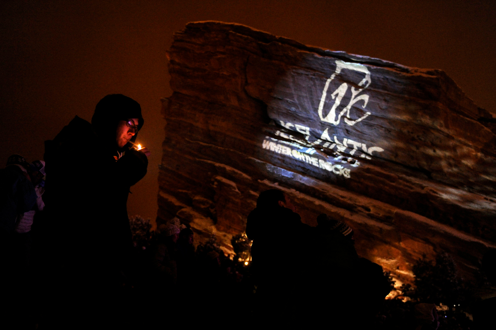 . A fan lights a cigarette as he watches Jurassic 5 perform during Winter on the Rocks at Red Rocks Amphitheatre on January 31, 2014 in Morrison, Colorado. (Photo by Seth McConnell/The Denver Post)