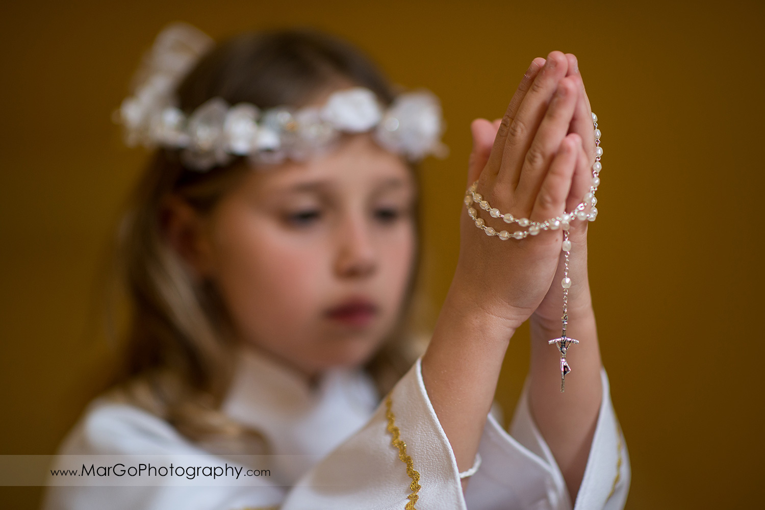 first communion girl in white alb holding rosary in folded hands in wooden San Jose church pews - focus on cross