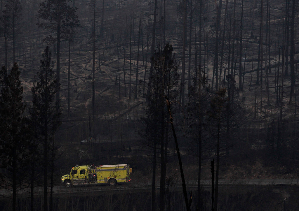 . A fire truck drives past trees burned during the Las Conchas fire in Los Alamos, N.M., Thursday, June 30, 2011.   (AP Photo/Jae C. Hong)