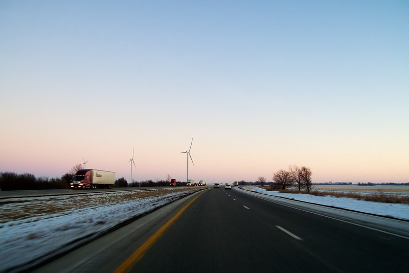 Wind turbines and Interstate 65. Indiana.  Cruising southbound on Interstate 65 in Indiana at twilight in winter.