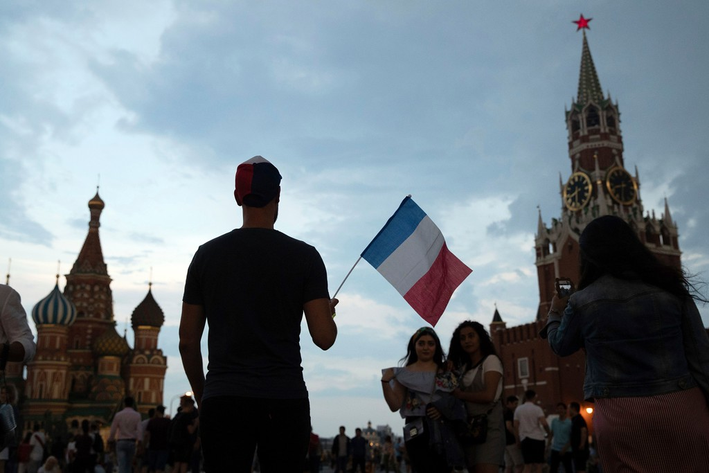 . A man walks with France national flag in Red square as France won the final match between France and Croatia at the 2018 soccer World Cup in the Luzhniki Stadium in Moscow, Russia, Sunday, July 15, 2018. (AP Photo/Pavel Golovkin)