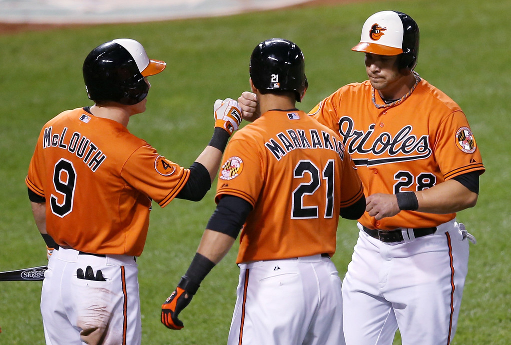 . BALTIMORE, MD - AUGUST 17: Steve Pearce #28 of the Baltimore Orioles celebrates scoring a run with teammates Nate McLouth #9 and Nick Markakis #21 during the third inning against the Colorado Rockies at Oriole Park at Camden Yards on August 17, 2013 in Baltimore, Maryland.  (Photo by Rob Carr/Getty Images)