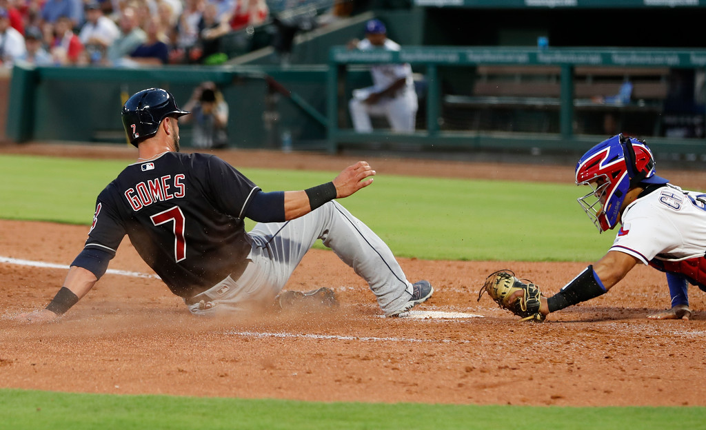. Cleveland Indians\' Yan Gomes (7) slides home ahead of a tag by Texas Rangers catcher Robinson Chirinos, right, on a double hit by teammate Francisco Lindor during the fifth inning of a baseball game, Saturday, July 21, 2018, in Arlington, Texas. (AP Photo/Jim Cowsert)