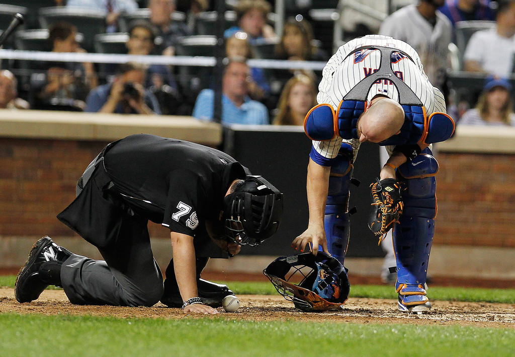 . Homeplate umpire Manny Gonzalez #79 is attended to by John Buck #44 of the New York Mets after being injured in the sixth inning during a game against the Colorado Rockies at Citi Field on August 6, 2013 at Citi Field in the Flushing neighborhood of the Queens borough of New York City.  (Photo by Mike Stobe/Getty Images)