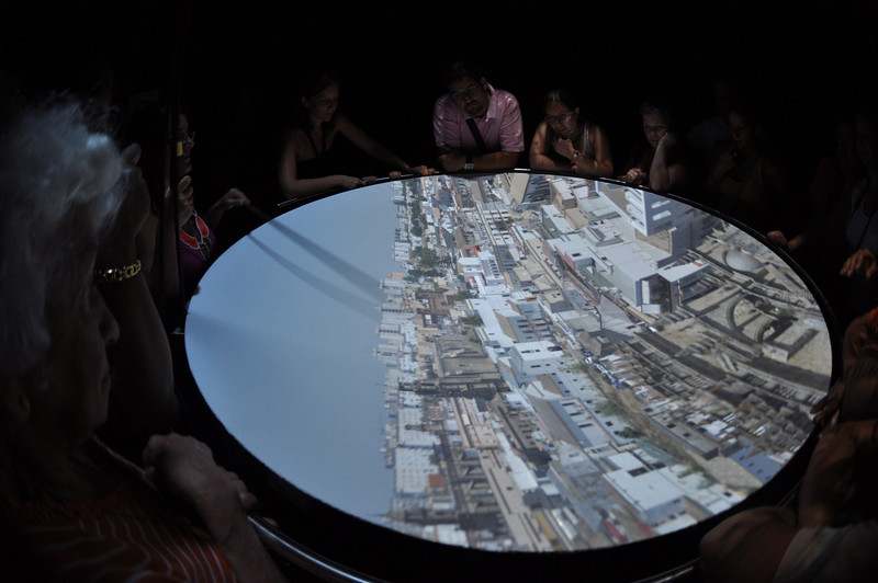 """This is a Camera Oscura - it's NOT a video - but a LIVE image of the city around you. It sits on top of a tower. It consists of a big mirror and a big lens. The mirror is pointed to any part of the city and it then beams back through the lens an image of the city. The lady holding those two ropes controls the pitch and angle of the mirror. The detail is FANTASTIC -- BETTER than HD. it's live you see birds flying, flags waving, clothelines move and people and cars move. It's as old as DaVinci. It may have been used by the Dutch Masters to """"calcar"""" draw by projecting the views into a canvas. Think of it as a HUGE camera (size of a room) that you go INSIDE of it.  I've always wanted to see a Camara Oscura since I was 10 or so and read about in Sherlock Holmes and other novels. The pictures are clear but you should see the video: AMAZING."""