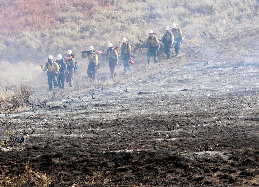 . A team of hotshots walk along a fire line near homes on Croy Road and the Rotorun ski hill west of Hailey Saturday Aug. 17, 2013. The Beaver Creek fire moved through the area in the early hours Saturday morning. (AP Photo/Idaho Statesman, Darin Oswald)