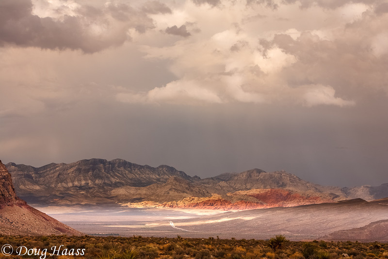 On the way back to Las Vegas, just outside of the city, I saw this off to my left.  Storm clouds were dropping some light rain and the sun was just kissing the red rock striata and caught my eye.