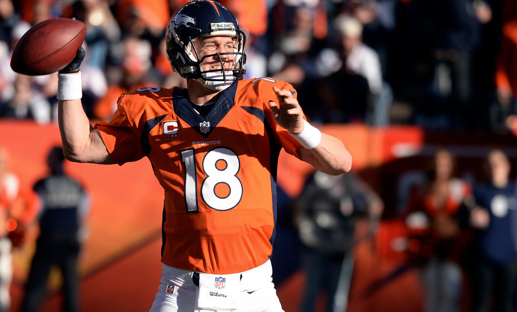 . Denver Broncos quarterback Peyton Manning (18) looks for a receiver during the third quarter.  The Denver Broncos vs. The New England Patriots in an AFC Championship game  at Sports Authority Field at Mile High in Denver on January 19, 2014. (Photo by Helen Richardson/The Denver Post)