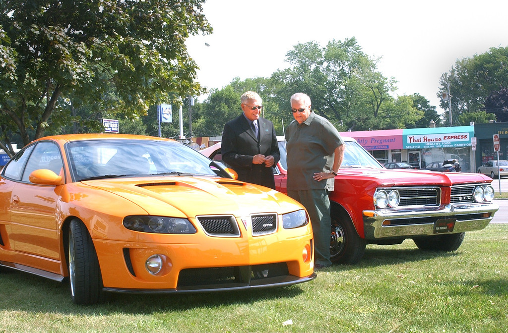 . Kip Wasenko, Exec. Director of Advance Concept Studios for General Motors with a 2004 Pontiac GTO and Ken Orlowski of Romeo with his \'64 GTO. The cas were on display at the kickoff of the 10th anniversary of the Woodward Dream Cruise.