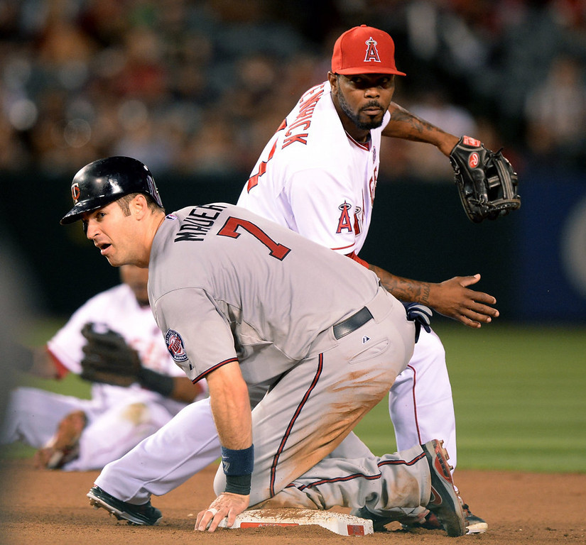 . ANAHEIM, CA - JULY 22:  Howie Kendrick #47 of the Los Angeles Angels and Joe Mauer #7 of the Minnesota Twins react to a force out at second during the seventh inning at Angel Stadium of Anaheim on July 22, 2013 in Anaheim, California.  (Photo by Harry How/Getty Images)