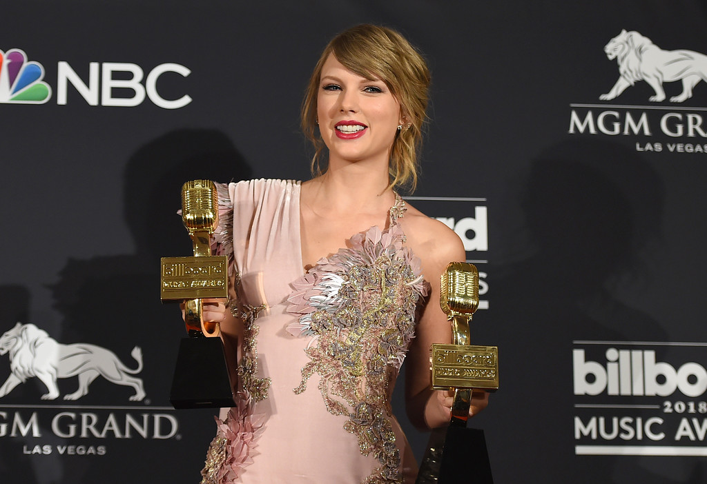 """. Taylor Swift poses in the press room with the award for top female artist and the award for top selling album for \""""reputation\"""" at the Billboard Music Awards at the MGM Grand Garden Arena on Sunday, May 20, 2018, in Las Vegas. (Photo by Jordan Strauss/Invision/AP)"""