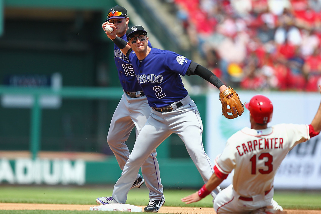 . ST. LOUIS, MO - MAY 11: Troy Tulowitzki #2 of the Colorado Rockies turns a double play over Matt Carpenter #13 of the St. Louis Cardinals in the third inning at Busch Stadium on May 11, 2013 in St. Louis, Missouri.  (Photo by Dilip Vishwanat/Getty Images)