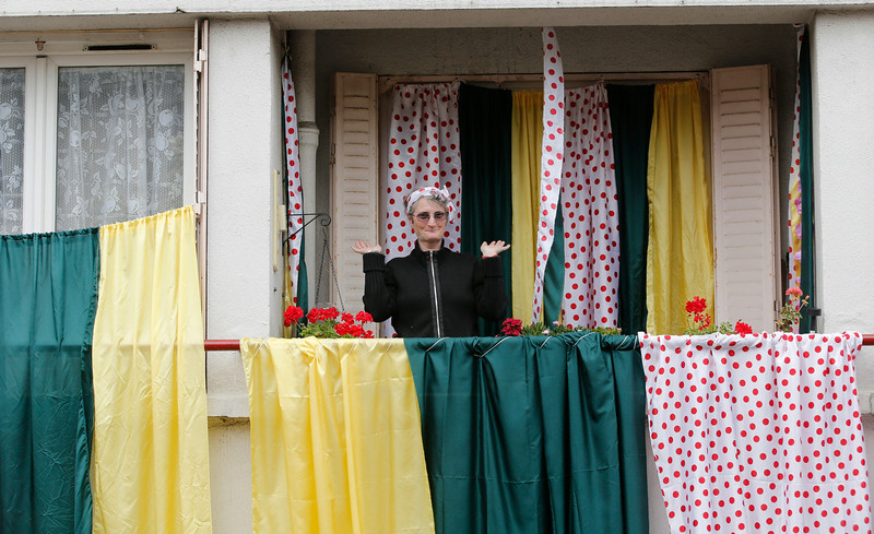. A woman stands on her balcony decorated with the best climber\'s dotted jersey colors gestures as the photographer takes pictures prior to the start of the eighth stage of the Tour de France cycling race over 161 kilometers (100 miles) with start in Tomblaine and finish in Gerardmer, France, Saturday, July 12, 2014. (AP Photo/Christophe Ena)