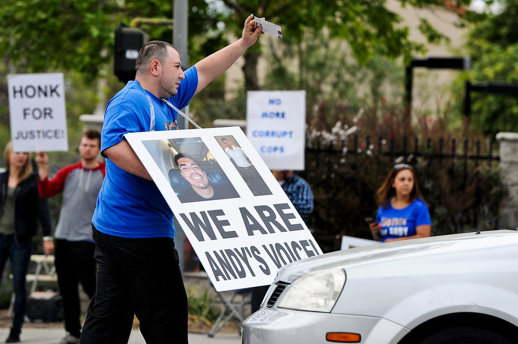 . Avila\'s bestfriend Julio Zaragoza, 27, of San Bernardino walks up to cars and passes out flyers as family members of Andres Avila and their supporters gather to protest the October 2011 police-involved shooting of Avila at the intersection of Garey and Holt Avenues in Pomona on Sunday, April 14, 2013. The group held signs against police corruption and marched to the Pomona police station. (Rachel Luna / Staff Photographer)