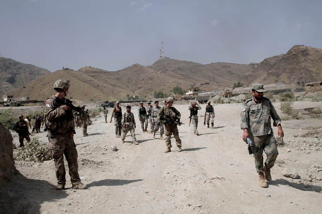 . U.S. forces patrol near the scene of an attack by militants on a U.S. base in the Torkham area near the Pakistan-Afghanistan border east of Kabul, Afghanistan, Monday, Sept. 2, 2013. The Taliban claimed responsibility for the strike on a U.S. base in Afghanistan near the border with Pakistan on Monday, setting off bombs, torching vehicles and shutting down a key road used by NATO supply trucks, officials said. Several people were killed.  (AP Photo/Rahmat Gul)