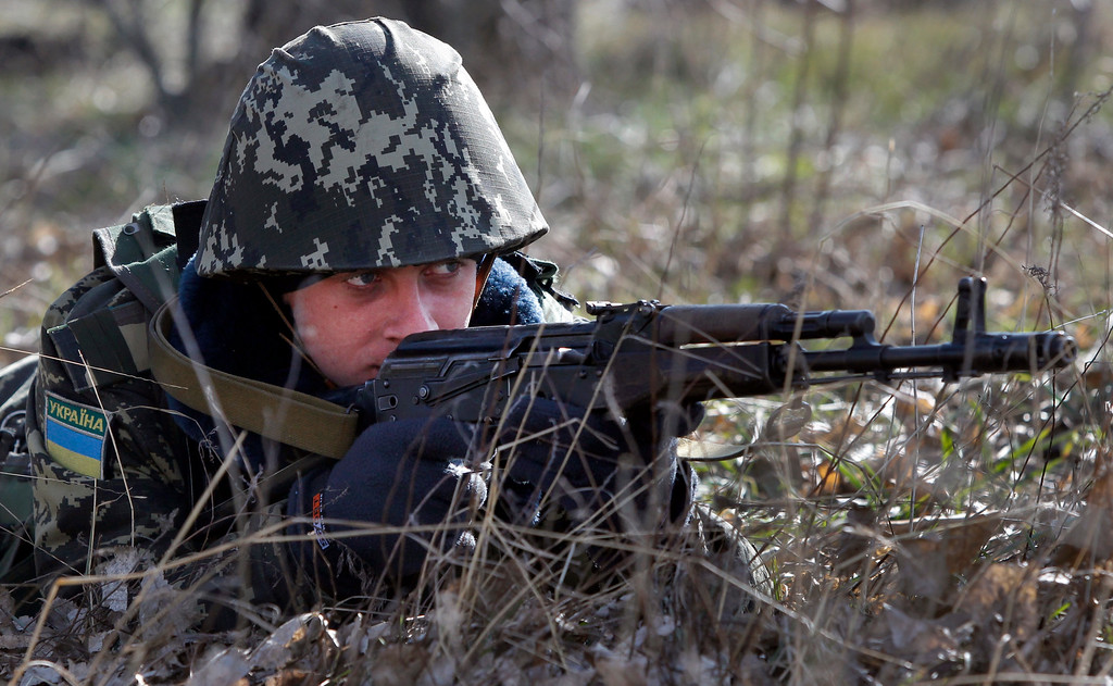 . A Ukrainian border guard takes  position during training at a military camp in the village of Alekseyevka on the Ukrainian-Russian border, eastern Ukraine, Friday, March 21, 2014.  (AP Photo/Sergei Grits)