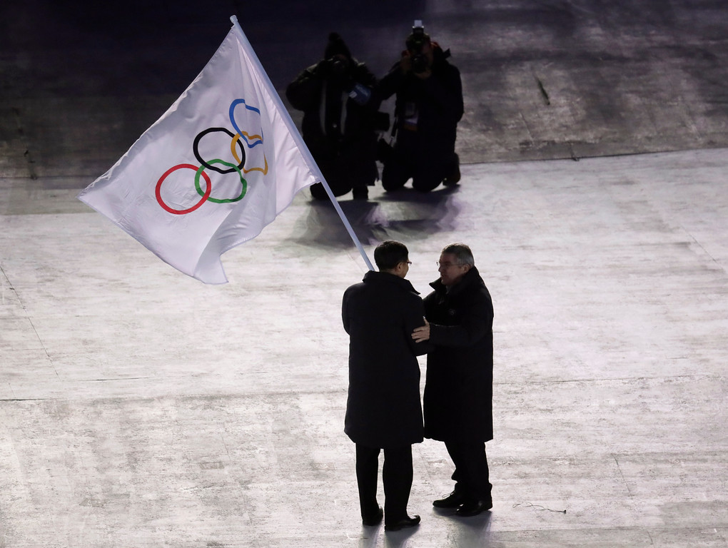 . International Olympic Committee President Thomas Bach, right, hands the Olympic flag to the mayor of Beijing Chen Jining, during the closing ceremony of the 2018 Winter Olympics in Pyeongchang, South Korea, Sunday, Feb. 25, 2018.(AP Photo/Aaron Favila)