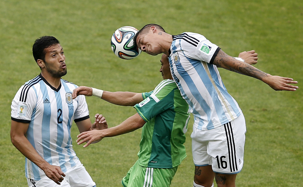 . Argentina\'s defender Ezequiel Garay (L) and Argentina\'s defender Marcos Rojo (R) challenge Nigeria\'s forward Peter Odemwingie (C) for the ball during the Group F football match between Nigeria and Argentina at the Beira-Rio Stadium in Porto Alegre on June 25, 2014,during the 2014 FIFA World Cup. ADRIAN DENNIS/AFP/Getty Images
