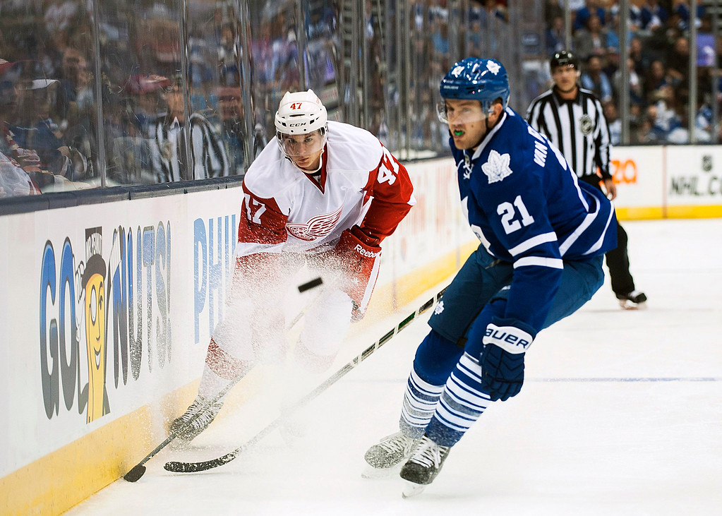 . Detroit Red Wings\' Alexey Marchenko, left, takes the puck downice past Toronto Maple Leafs\' James van Riemsdyk during first-period preseason NHL hockey game action in Toronto, Friday, Oct. 3, 2014. (AP Photo/The Canadian Press, Aaron Vincent Elkaim)