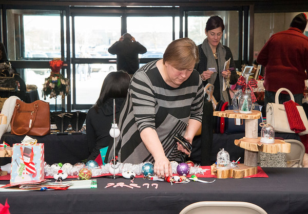 12/12/19 Wesley Bunnell | StaffrrA shopper examines one of the many tables during the Holiday Craft Fair at 1 Liberty Square on Thursday afternoon.
