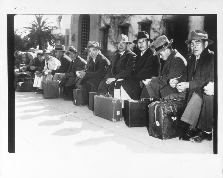 """""""On Their Way Out! -- Above photo show group of Japanese rounded up by FBI agents at Santa Barbara and dejectedly sitting with their baggage, awaiting removal for hearings in Los Angeles.""""--caption on photograph"""
