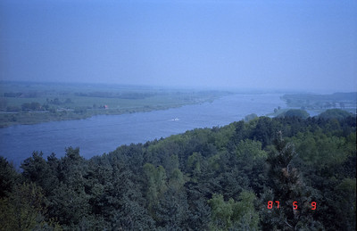 I believe this photo was taken from a tall viewing platform erected on the West German side to afford an excellent view into the area of the DDR.  Not sure if that is a commercial vessel cruising just this side of the center of the Elbe river.