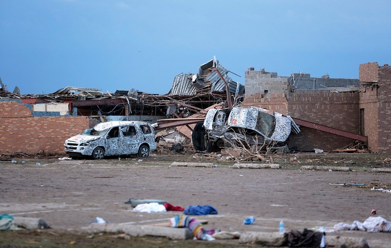 . Cars lie around the northeast corner of Plaza Towers Elementary school after it was damaged by a tornado May 21, 2013 in Moore, Oklahoma. The town reported a tornado of at least EF4 strength and two miles wide that touched down yesterday killing at least 24 people and leveling everything in its path. U.S. President Barack Obama promised federal aid to supplement state and local recovery efforts.  (Photo by Brett Deering/Getty Images)