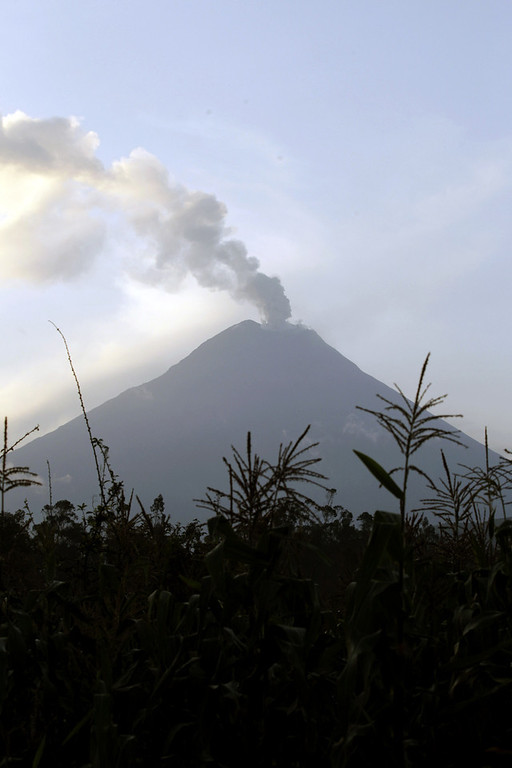 . An ash-filled plume rises from the Tungurahua volcano as seen from Huambalo, Ecuador, Monday, Dec. 17, 2012.  The country\'s National Geophysics Institute says that a constant plume of gas and ash is rising about half a mile (1 kilometer) above the crater, with ash falling on nearby communities.  (AP Photo/Dolores Ochoa)