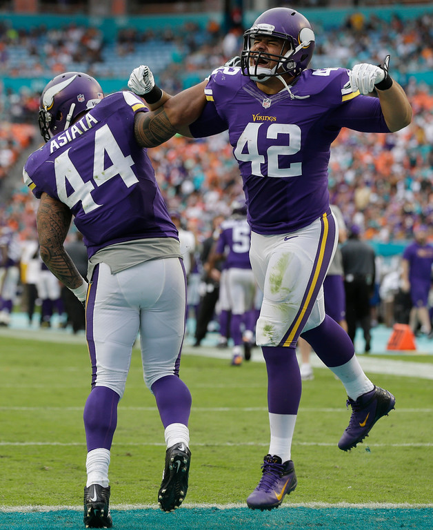. Minnesota Vikings running back Matt Asiata (44) and fullback Jerome Felton (42) celebrate Asiata\'s touchdown during the second half of an NFL football game against the Miami Dolphins, Sunday, Dec. 21, 2014, in Miami Gardens, Fla. (AP Photo/Lynne Sladky)