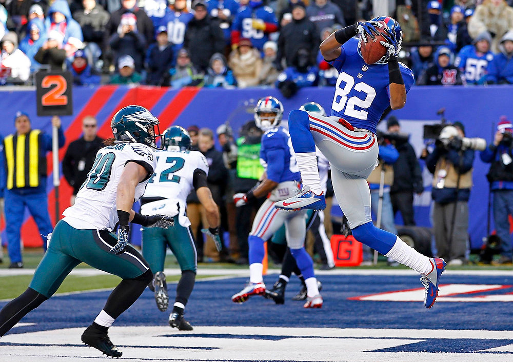 Description of . New York Giants Rueben Randle (R) catches a touchdown pass next to Philadelphia Eagles Colt Anderson (L) in the first quarter during their NFL football game in East Rutherford, New Jersey, December 30, 2012. REUTERS/Gary Hershorn