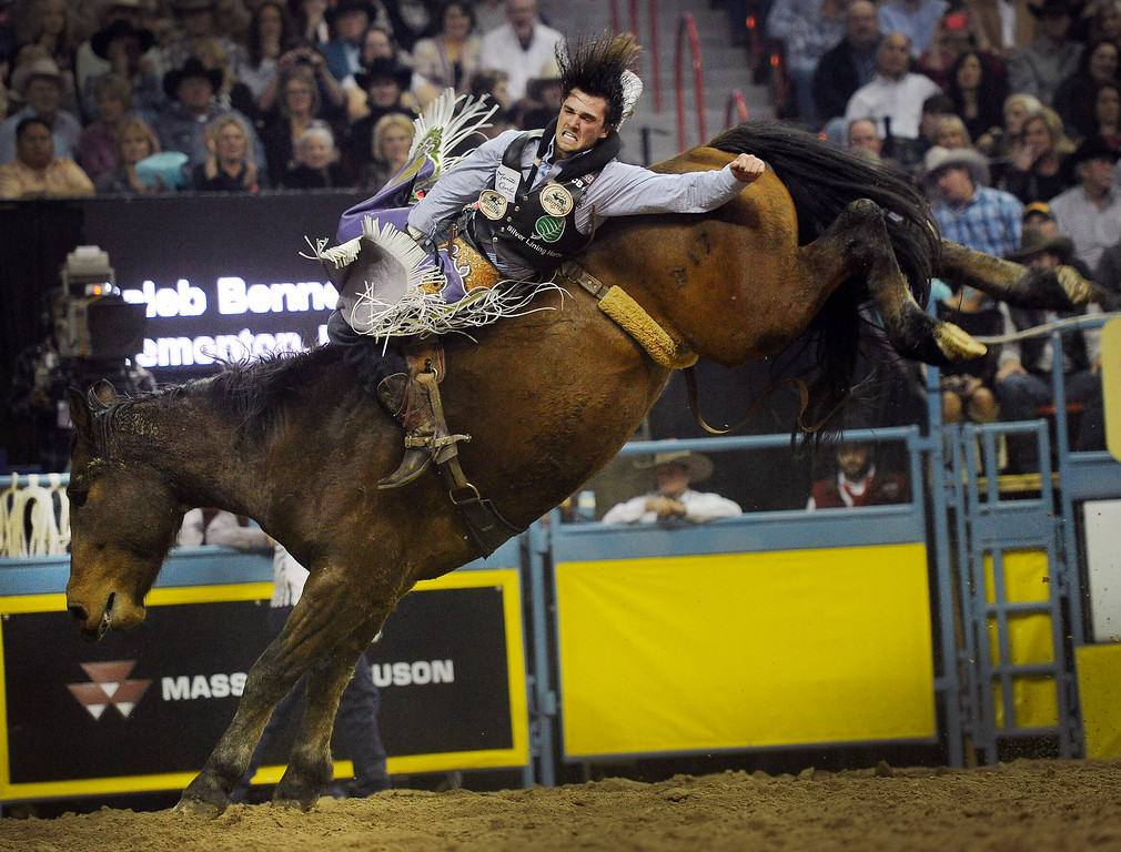 . Caleb Bennett of Tremonton, Utah competes in the bareback riding during the third go-round of the Wrangler National Finals Rodeo on Saturday, Dec. 6, 2014, in Las Vegas. (AP Photo/Las Vegas Review Journal, David Becker)