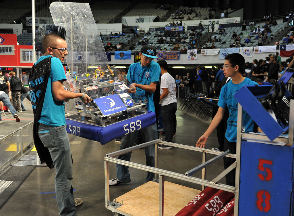 . 3/22/13 - A team removes their robot from the arena during the robotic competition on Friday morning. More than 1,500 high school students from California, Hawaii and Chile are competing in the 22nd FIRST Robotics Los Angeles Regional Competition at the Long Beach Arena.This years robotic task is throwing discs for points. Photo by Brittany Murray / Staff Photographer