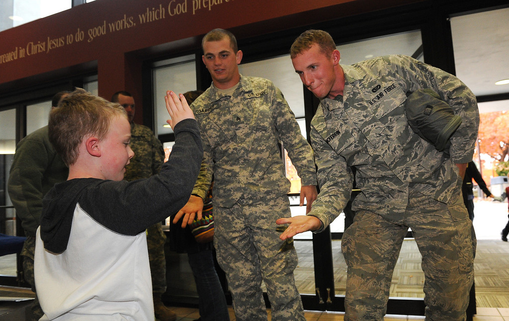 . LONGMONT, CO - OCTOBER 29:   Tanner Murphy, middle and Colton McFerrin, both of the Kansas National Guard get high fives from Lyons resident Benjamin Taylor, 7,  as they arrive at the Life Bridge Community Church in  Longmont, Co on October 29, 2013.  They were coming to be part of a celebration  held to thank members of the military, law enforcement, firefighters and members of Colorado Department of Transportation for all their work during and after the floods.   (Photo By Helen H. Richardson/ The Denver Post)