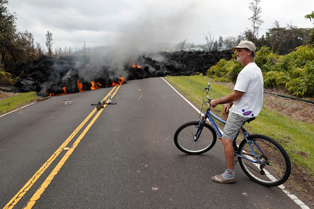 . Leilani Estates resident Sam Knox watches the lava stretch across the road, Saturday, May 5, 2018, in Pahoa, Hawaii. Knox\'s home is less than a few hundred yards from the lava flow and he does not have any plans to evacuate. Knox is hopeful the lava will not take his home. (AP Photo/Marco Garcia)