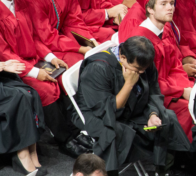 A teacher engrossed in his phone during the long list of announced graduates -- Noah Friedlander - June 6, 2017 graduation from Montgomery Blair High School - Magnet Program for Math, Science, and Computer Science, Xfinity Center, University of Maryland, College Park.