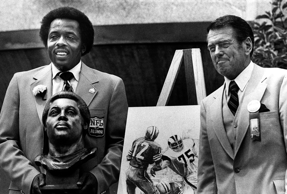 . In this Aug. 2, 1980 file photo, former Los Angeles Rams defensive end Deacon Jones, left, poses with his bust and a drawing of him in action after enshrinement in the Pro Football Hall of Fame in Canton, Ohio. (AP Photo/File)