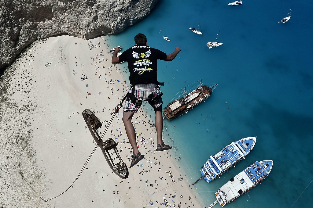. Lukas Michul, a member of the \'dream walker\' group jumps from atop the rugged rocks overlooking the azure waters of Navagio beach, one of the Greece\'s most renowned leisure spots on the popular tourist island of Zakynthos on June 23, 2014.  This is rope jumping -- part diving, part rock climbing, with a touch of engineering. The aim of the project is to dream jump in 80 places with most ravishing nature and architecture all over the world .They plan to stage their next leaps at a cave complex in Croatia, a French viaduct, skyscrapers in Las Vegas and Johannesburg, and the Grand Canyon. AFP PHOTO /  LOUISA GOULIAMAKI/AFP/Getty Images