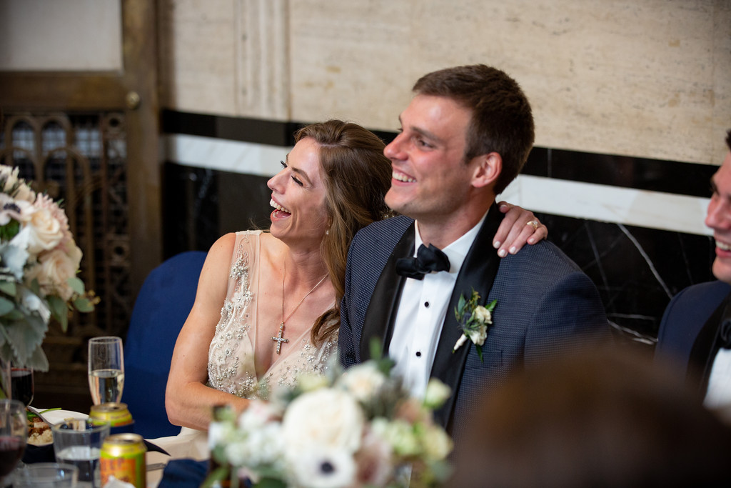 bride and groom smile towards the stage as they are toasted on their wedding night