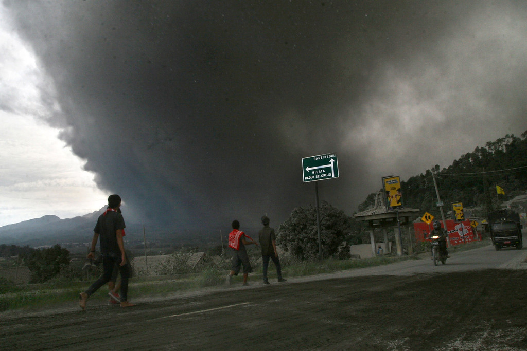 . Residents evacuate under a massive plume of hot ash clouds spewing from Mount Kelud volcano as seen from Malang district in East Java province on February 14, 2014.    AFP PHOTO / AMAN ROCHMAN/AFP/Getty Images