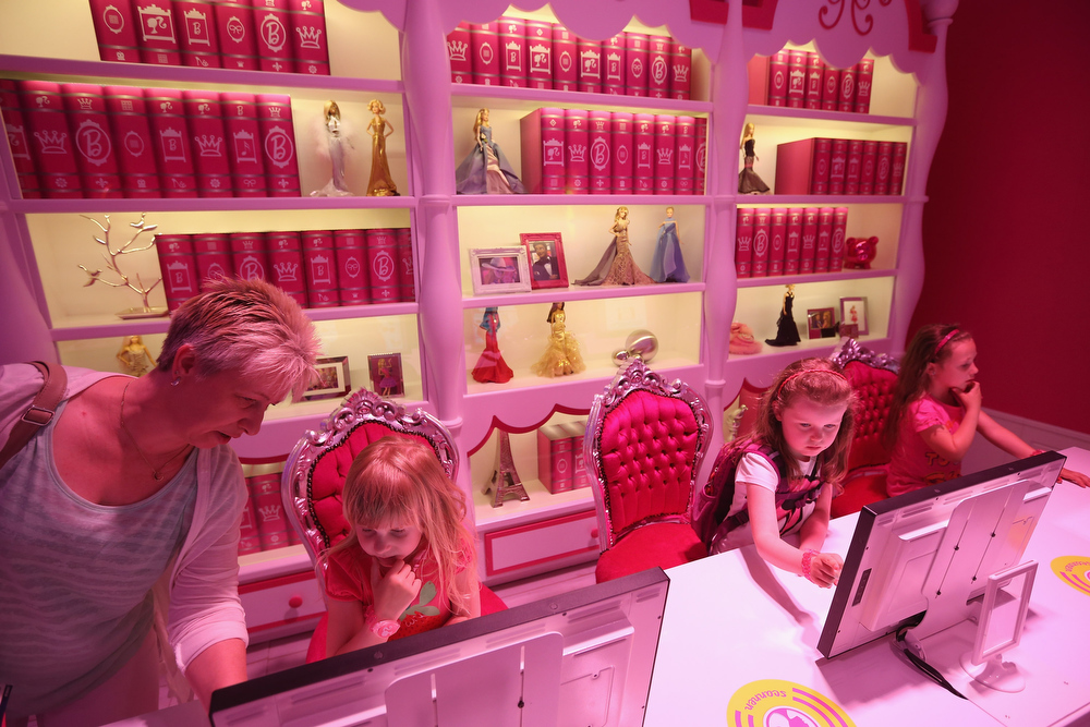 . Josi (L), Lara (C) and Luna, all 6, try out computer terminals in Barbie\'s library at the Barbie Dreamhouse Experience on May 16, 2013 in Berlin, Germany. The Barbie Dreamhouse is a life-sized house full of Barbie fashion, furniture and accessories and will be open to the public until August 25 before it moves on to other cities in Europe.  (Photo by Sean Gallup/Getty Images)