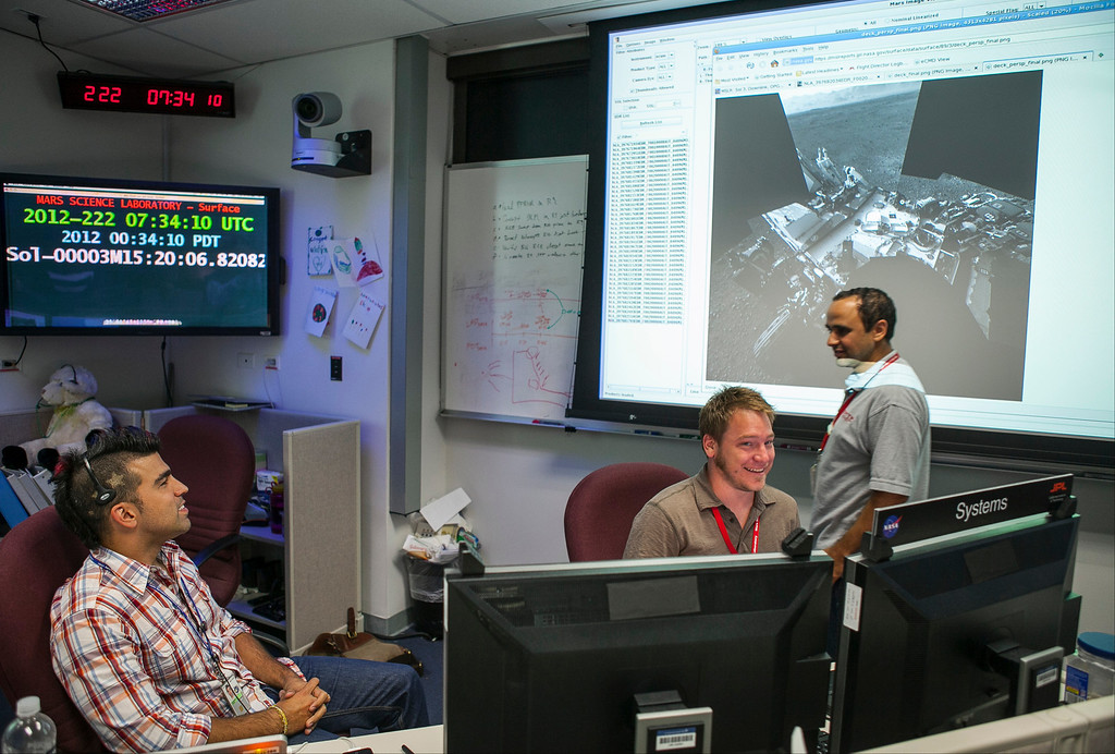 ". FILE - In this Thursday, Aug. 9, 2012 file photo, Bobak Ferdowsi, a flight director for the Mars Curiosity rover, known as the ""Mohawk Guy,\"" talks with colleagues at his workstation at NASA\'s JPL in Pasadena, Calif. (AP Photo/Damian Dovarganes)"