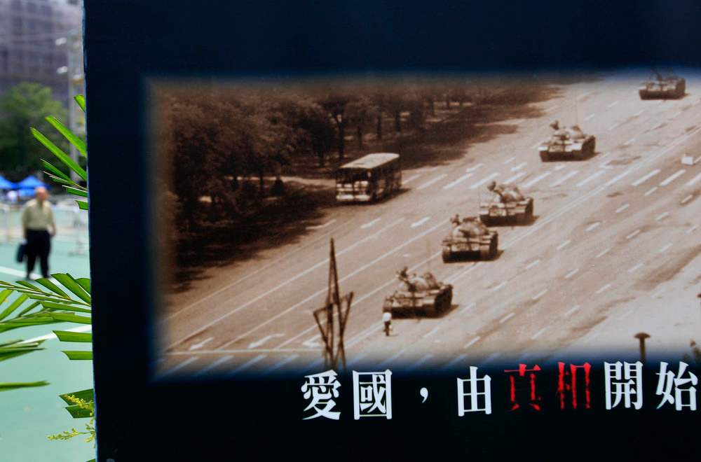 """. A picture showing a man blocking a line of tanks during the 1989 pro-democracy movement in Beijing is displayed at Hong Kong\'s Victoria Park Tuesday, June 4, 2013. Tens of thousands of people were expected to gather Tuesday evening at Victoria park in the former British colony, holding candles aloft to remember those killed when their protests in central Beijing were crushed by the Chinese military on June 4, 1989. Commemorations of the crackdown are suppressed everywhere else in China. The writing at the bottom of the picture reads \"""" Love the country start from the truth.\"""" (AP Photo/Vincent Yu)"""