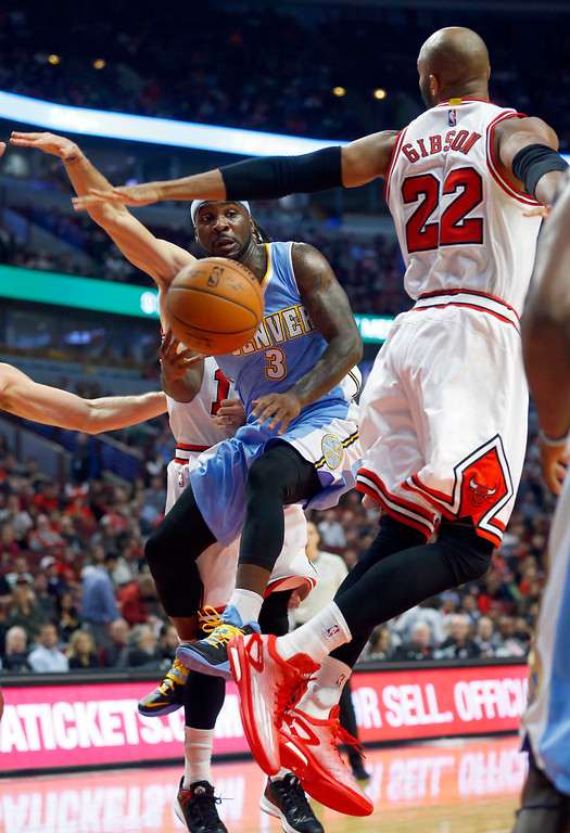 . Denver Nuggets guard Ty Lawson (3) makes a pass by Chicago Bulls forward Taj Gibson (22) during the first half of a pre-season NBA basketball game in Chicago, on Monday Oct. 13, 2014. (AP Photo/Jeff Haynes)