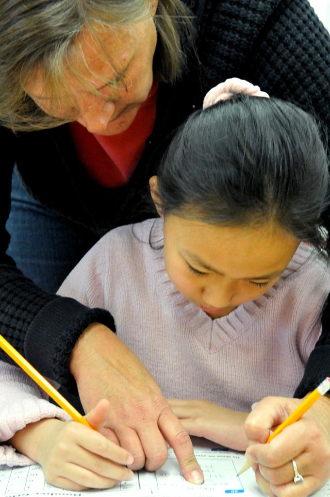 . Para-professional Dawn Schmidt helps third grader Crystal Moua solve a math problem in Tara Kuehlwein\'s classroom at Frost lake Elementary.  (Pioneer Press: John Doman)